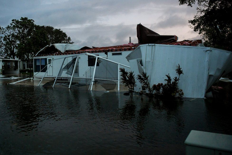 Flood water from Hurricane Irma surround a damaged mobile home in Bonita Springs, Florida, 10 September