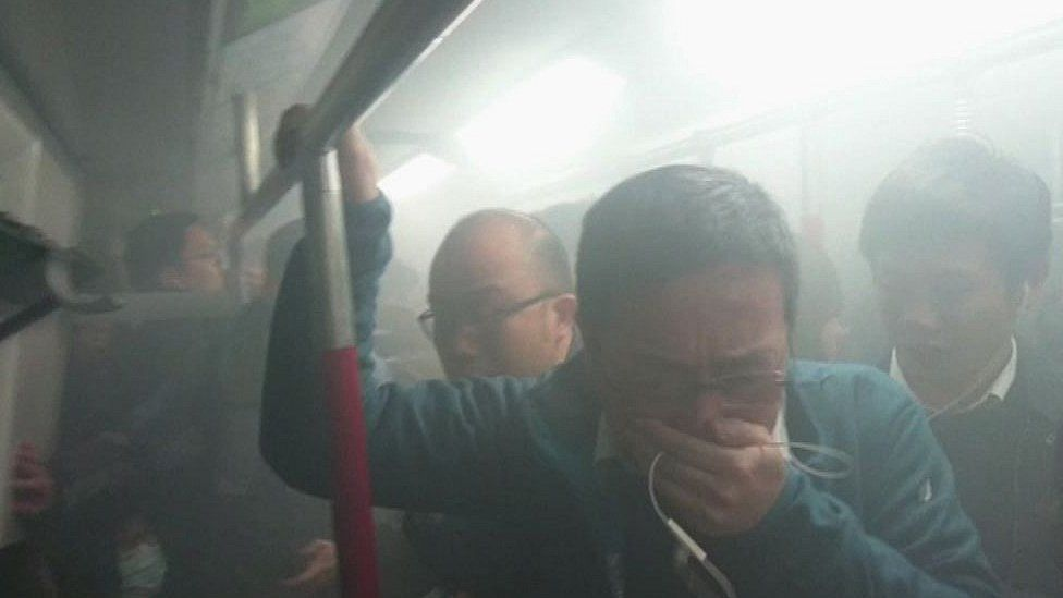 People cover their faces from smoke after a fire broke out inside an MTR metro train in Hong Kong on February 10, 2017