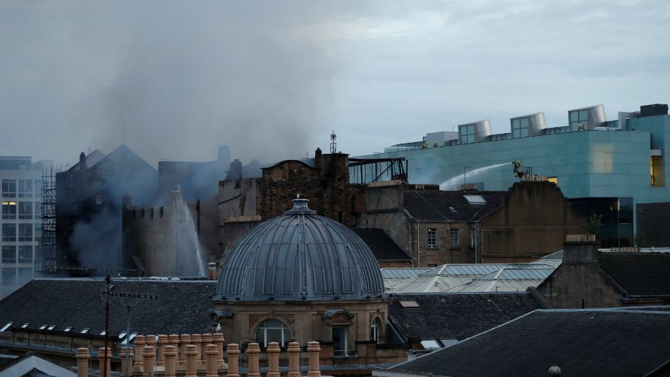 Firefighters continue to battle the fire as dawn breaks over Glasgow