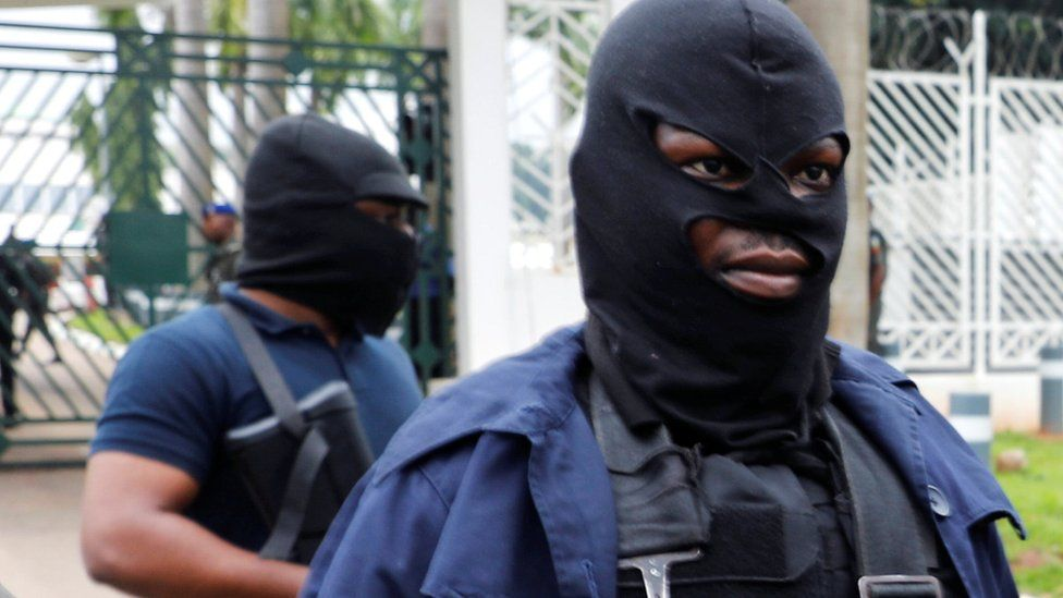 Masked men outside parliament in Nigeria