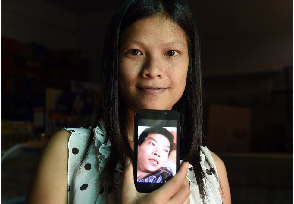 This photo taken on 30 July 2014 shows shows 21-year-old Vietnamese bride Vu Thi Hong Thuy posing with a photo of her Chinese husband in Weijian village, in China's Henan province.