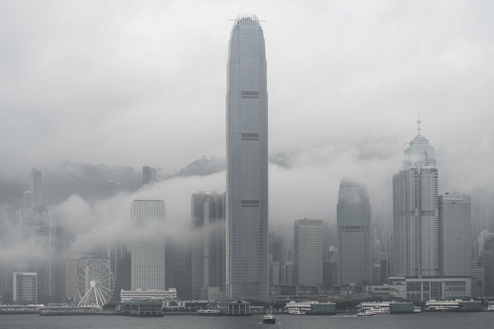 The International Finance Center tower (C) and the city skyline are seen shrouded in fog in Hong Kong on 9 March 2016
