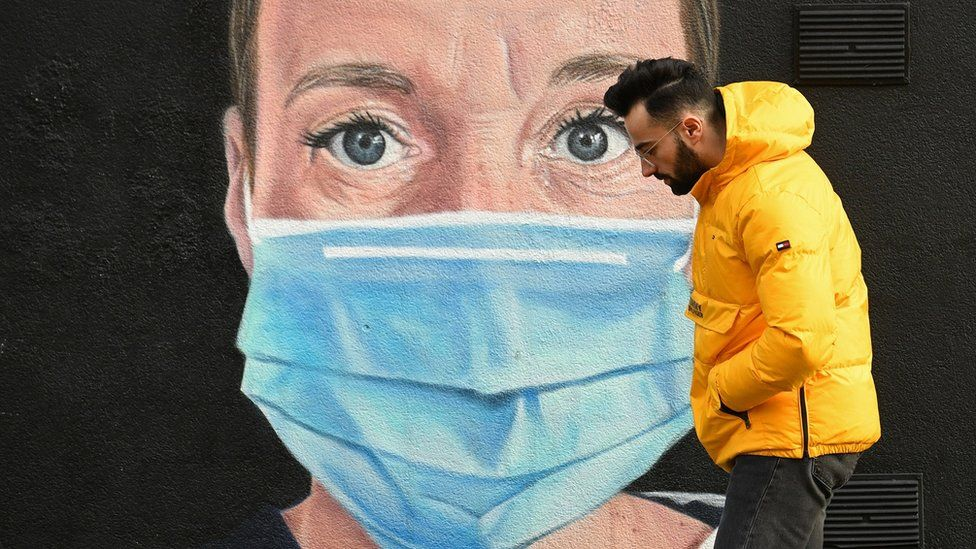 A man wearing walks past street art of an NHS worker in Manchester on 5 January 2021