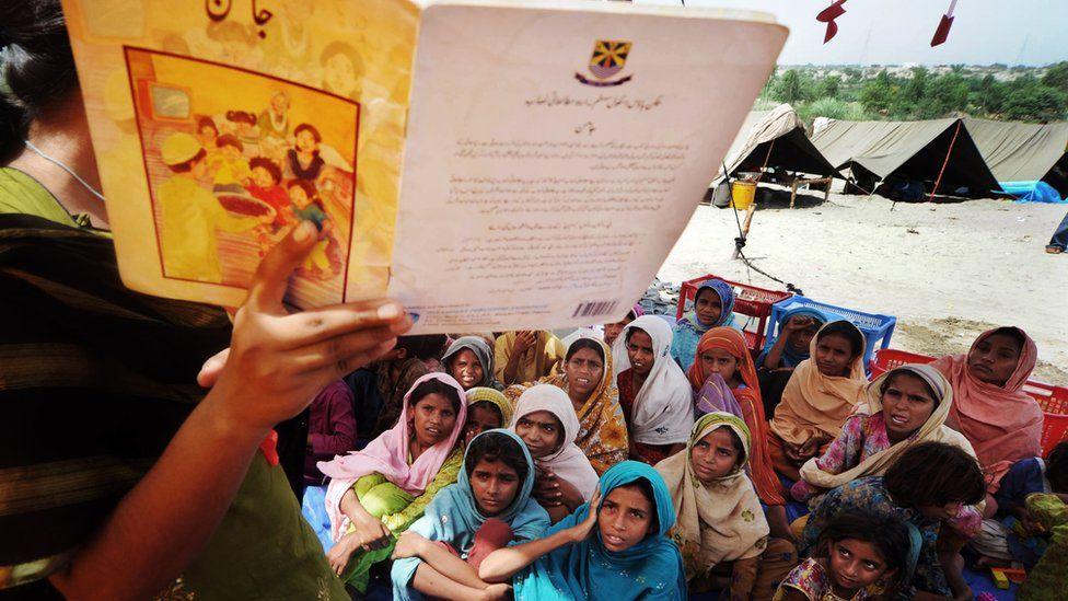 Pakistani girls listen to a teacher at a makeshift tent school