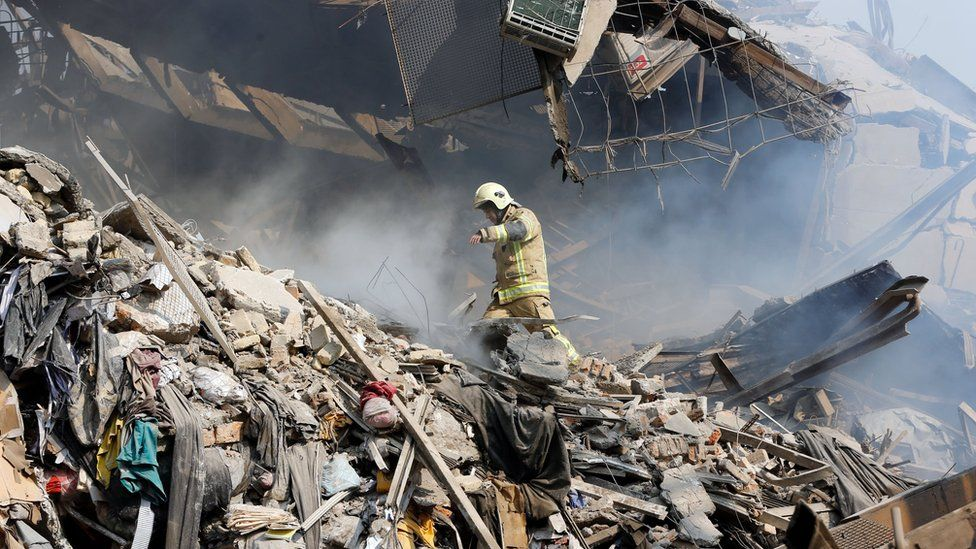 A firefighter stands in the rubble of the collapsed Plasco building in Tehran, Iran (19 January 2017)