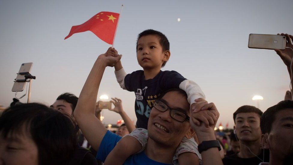 A man carries his son on his shoulders to see the lower of the flag on Tiananmen square in Beijing on September 28, 2017.