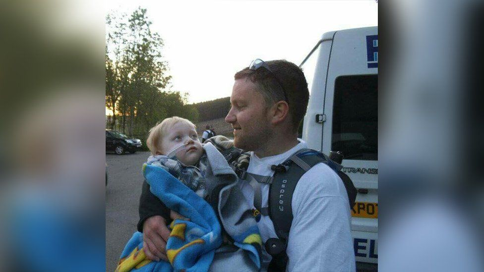 Brad Watson cradling his ill son Archie