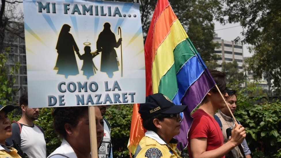 A gay community member marches next to members of the National Front for the Family