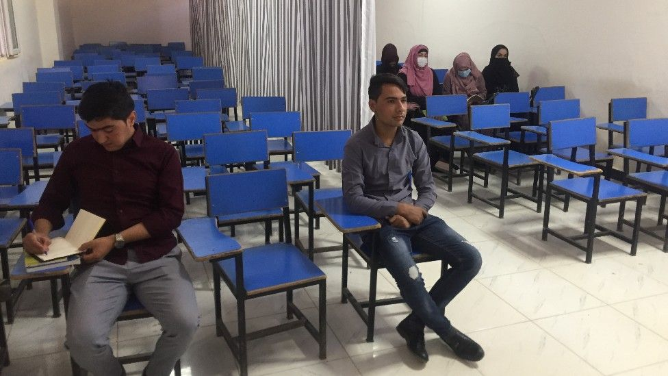 University students sit in a classroom with a curtain between the male and female students