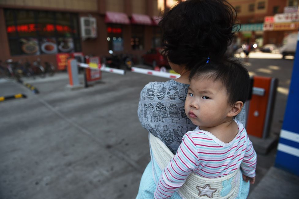 This photo taken on June 24, 2015 shows a woman carrying a baby in Yanji, in China's northeast Jilin province