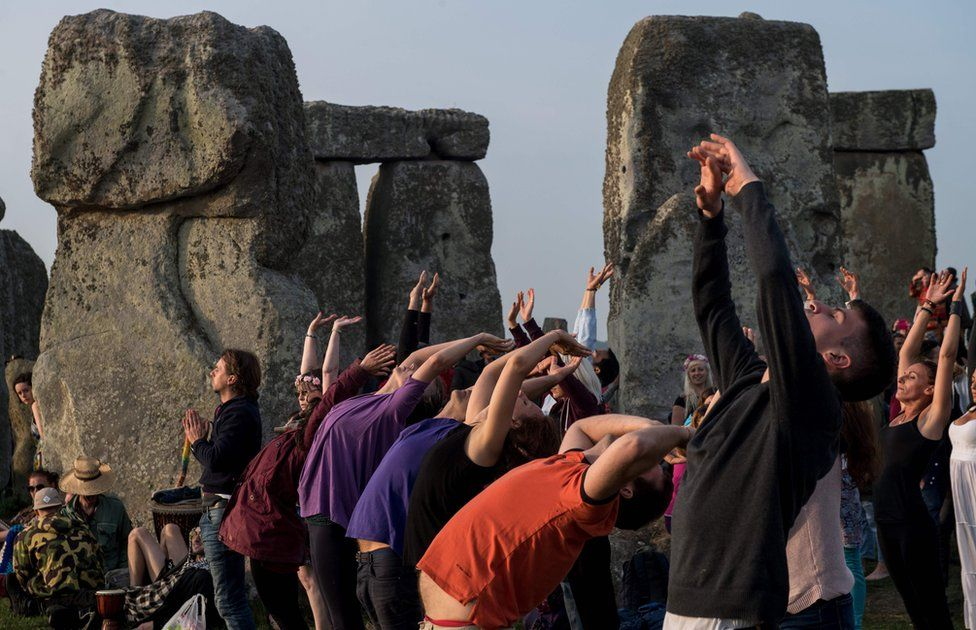 Revellers practice yoga as the sun rises during the pagan festival of Summer Solstice at Stonehenge in Wiltshire, southern England on June 21, 2017