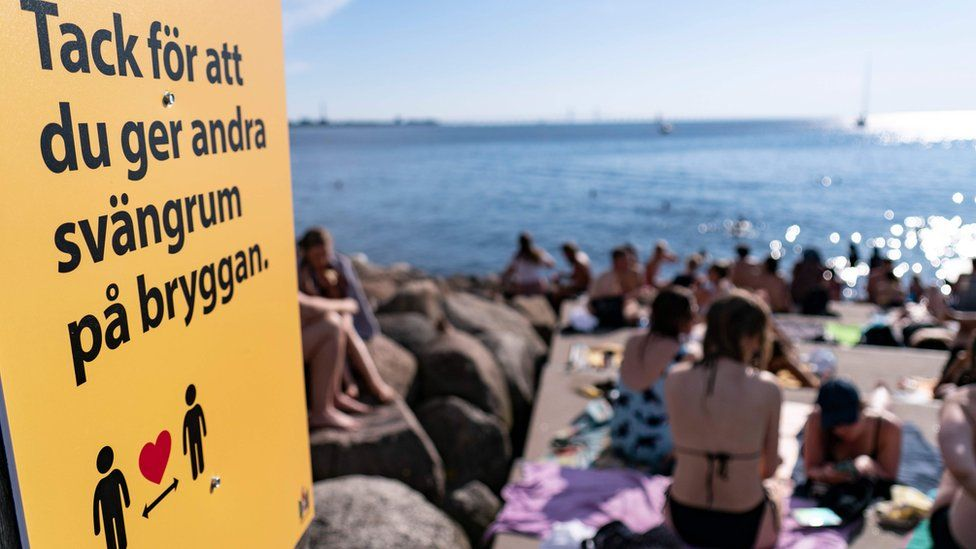 Heatwave in Malmo: An information sign ask people to keep social distance due to the corona pandemic