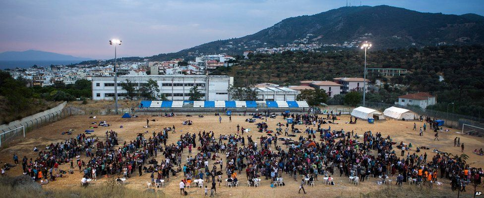 Refugees and migrants wait for their registration and the issuing of travel documents at a soccer stadium in Mytilene, on the northeastern Greek island of Lesbos, on 8 Sept 2015