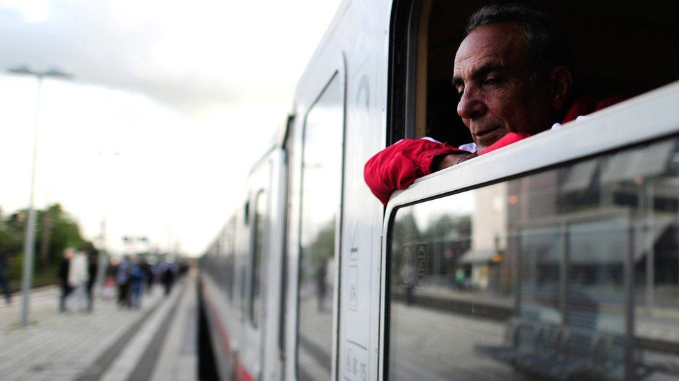 A Syrian refugee looks out of train window on arrival at the train station in Celle, Germany