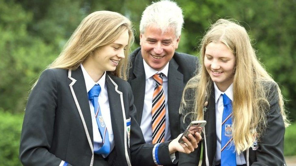Eastwood High School pupils Clare Wallace (right) and Erin Wallace with head teacher Stuart Maxwell