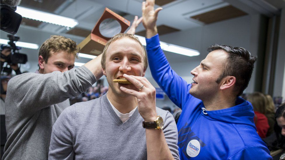 A previous supporter of Democratic presidential candidate Martin O'Malley eats a cookie as he is persuaded to support Democratic presidential candidate Sen. Bernie Sanders during caucus night at the State Historical Society of Iowa, on Monday, Feb. 1, 2016 in Des Moines, Iowa.