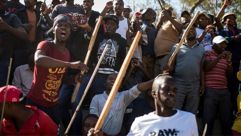 A group of Zulu men residing at the Jeppe Hostel shout and wave sticks during a speech given by the Police Minister General Bheki Cele in JeppesTown, on 3 September 2019 in Johannesburg.