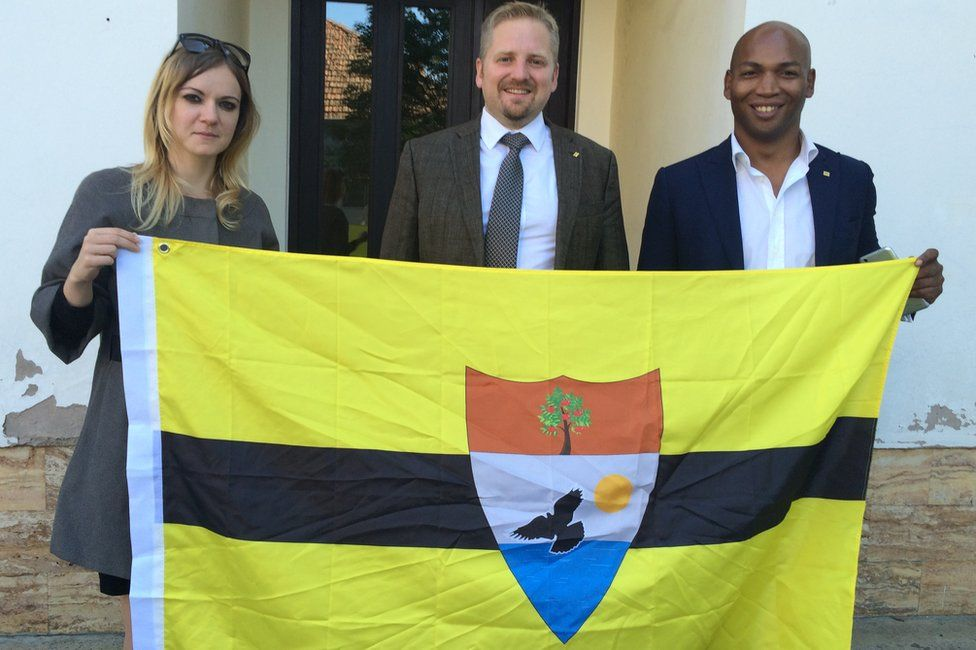 Vit Jedlicka (centre) holds a Liberland flag with former Liberland foreign minister Jose Miguel Maschietto (right) and his lawyer