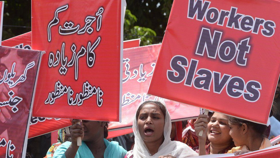 Pakistani labour union workers hold placards and shout slogans as they march during a May Day rally