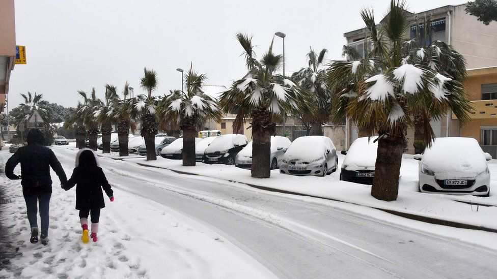 A woman walks with a child down a snow-covered road in Palavas-les-Flots, in the south of France, on February 28, 2018. Europe remained on February 28 gripped by a blast of Siberian weather, accounting for at least 24 deaths and carpeting palm-lined Mediterranean beaches in snow.