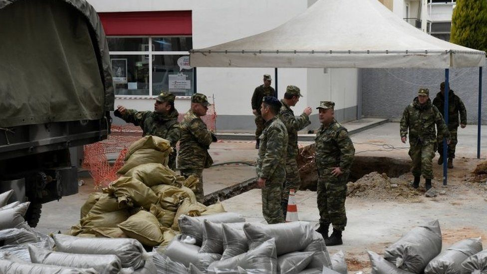 Military officers unload sacks of sand next to a hole in the ground (where a World War Two bomb was found in Thessaloniki (10 February 2017)