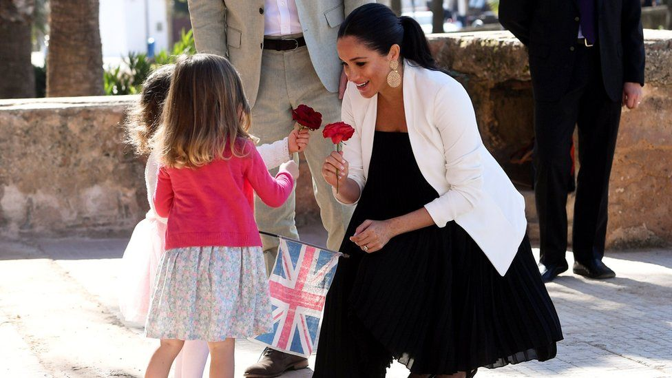 Duchess of Sussex is given flowers by two children during a visit to Morocco