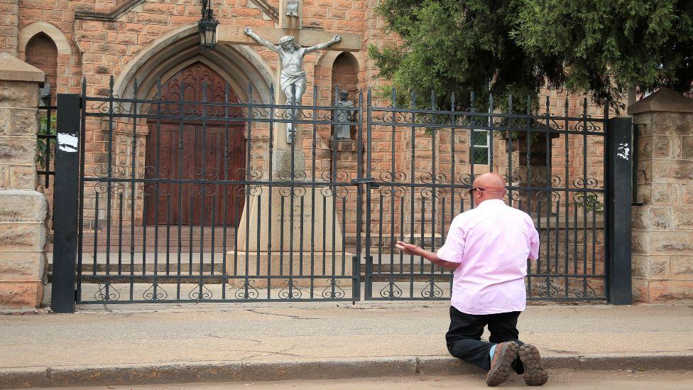 A parishioner prays outside a closed church in Zimbabwe