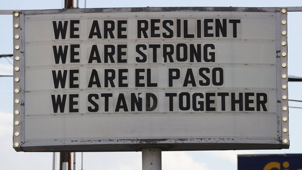 """A sign is posted near the scene of the mass shooting at El Paso, which reads: """"We are resilient, we are strong, we are El Paso, we stand together."""""""