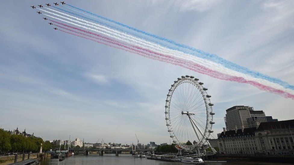 The Royal Air Force Red Arrows pass over the London Eye on the bank of the River Thames during a flypast in central London on 08 May 2020