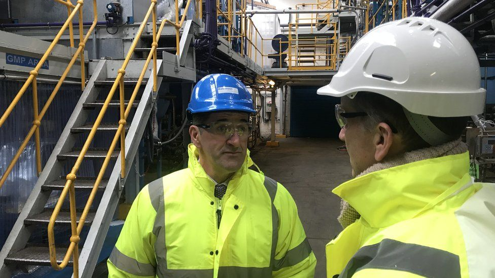 close up two men in hi vis and hard hats at factory talking