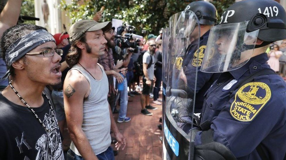 Virginia State Police wear body armour and use riot shields while keeping crowds away from alt-right blogger Jason Kessler after he tried to hold a news conference on 13 August 2017