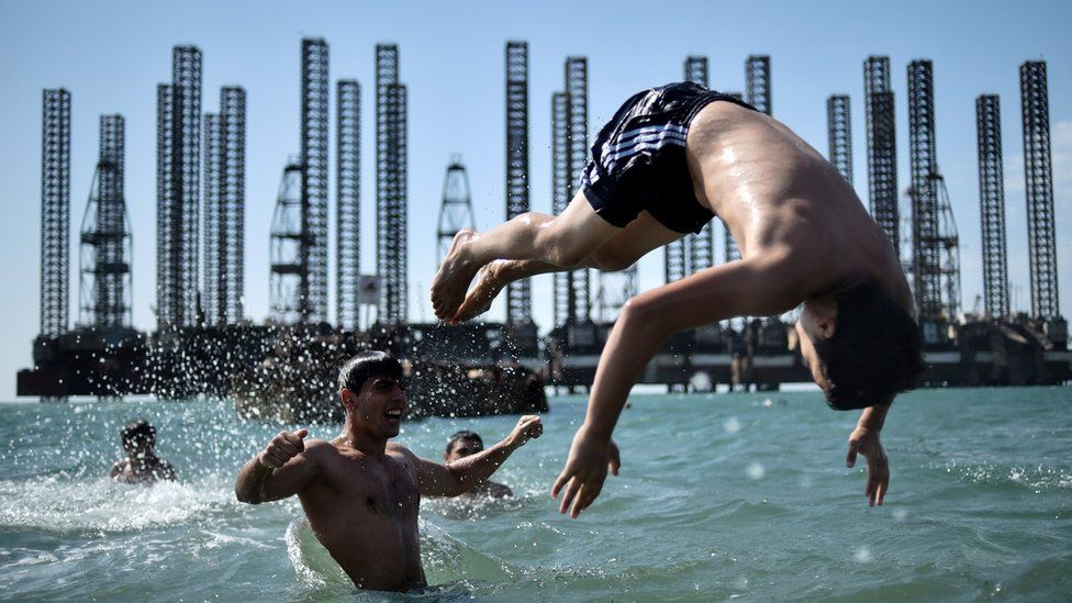 Teenagers from a boxing school take part in a training session on the shores of the Caspian Sea near Soviet oil rigs in the Azerbaijani capital Baku on June 27, 2015.