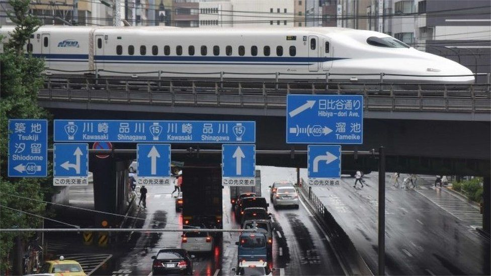 A Shinkansen bullet train moves on tracks above traffic in Tokyo on August 14, 2017.