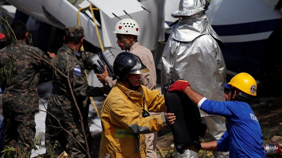 Rescue workers recover the luggage from the wreckage of a Gulfstream G200 aircraft that skidded off the runway