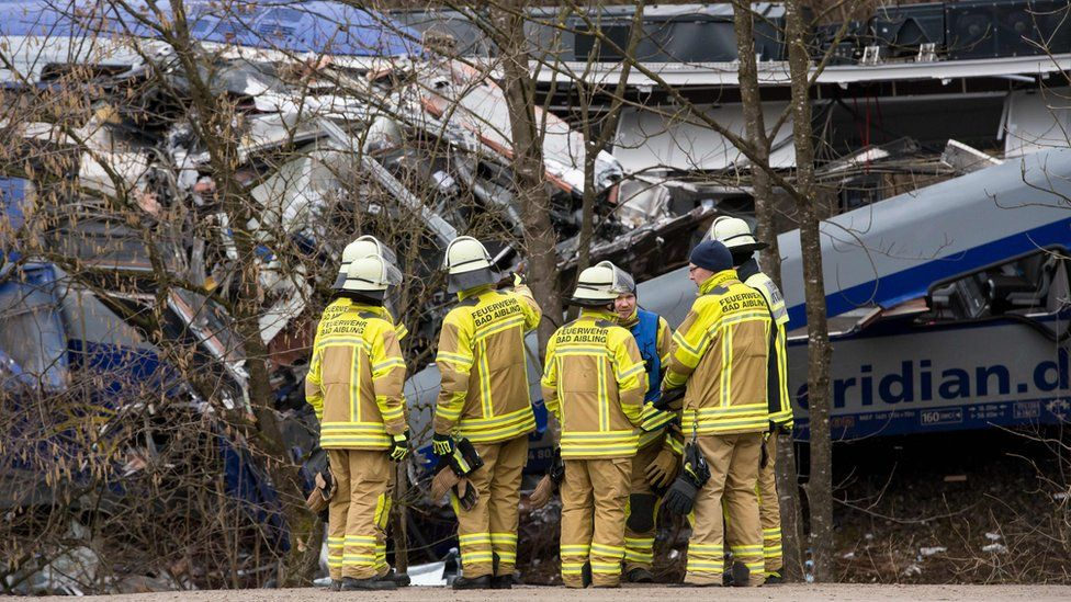 Rescue workers stand near the wreckage of two trains at Bad Aibling (9 Feb)