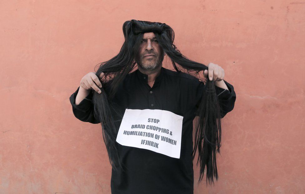 "Ahsan Antoo wears a wig of long hair while holding a sign that says ""stop braid chopping and humiliation of women"" in Kashmir"