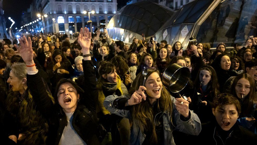 Women in Spain shout and make noise by hitting pots and pans as they mark the start of the International Women's Day in Sol Square, 8 March 2020