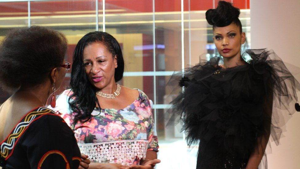 BBC presenter Veronique Edwards talks to designer Mary Martin while a model poses in her design behind her