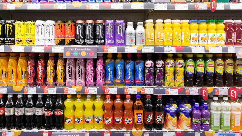 Refrigerantes e outras bebidas em prateleira de um supermercado