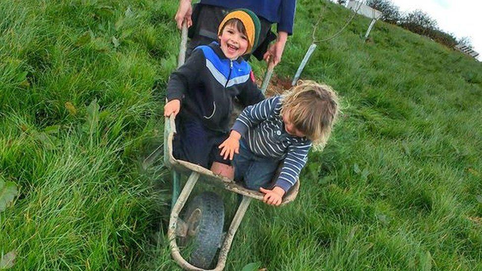 Two small boys in wheel barrow