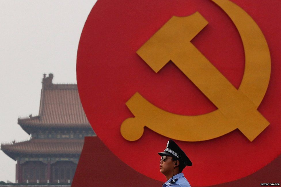 A policeman patrols under a giant communist emblem on the Tiananmen Square on 28 June 2011 in Beijing, China