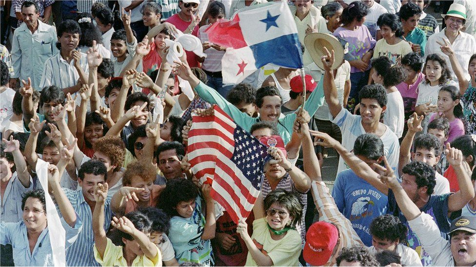 A large number of Panamanians opposed to General Manuel Antonio Noriega wave American and Panamanians flags outside a military post 22 December 1989.