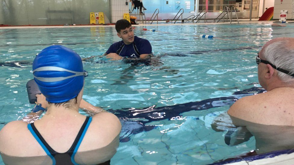 A swimming instructor teaching a class