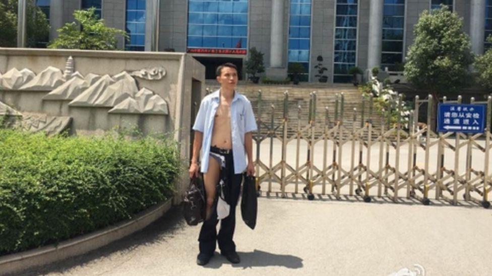 A photo showing Wu Liangshu in a ripped shirt and trousers