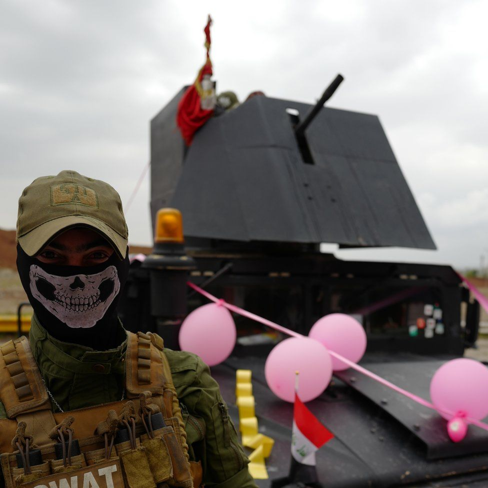 A SWAT officer with a skull mask over the lower half of his face stands in front of a military vehicle bedecked with pink balloons