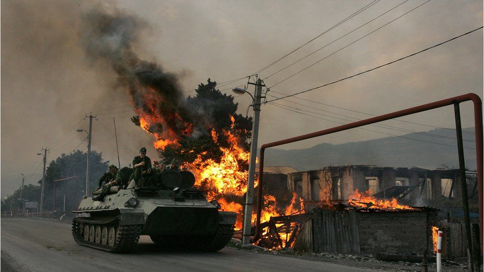Russian armoured troop carrier next to house set on fire by South Ossetian militia in the village of Kvemo-Achebeti, Georgia (file photo - August 2008)