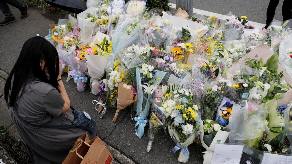 A woman prays in front of a row of flowers placed for victims of the torched Kyoto Animation building