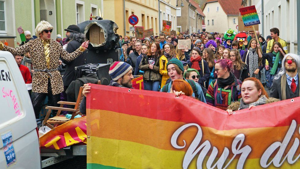 A crowd of people in a huge variety of bright colours and rainbow attire gather in the small street of Ostritz, waving placards and bearing banners