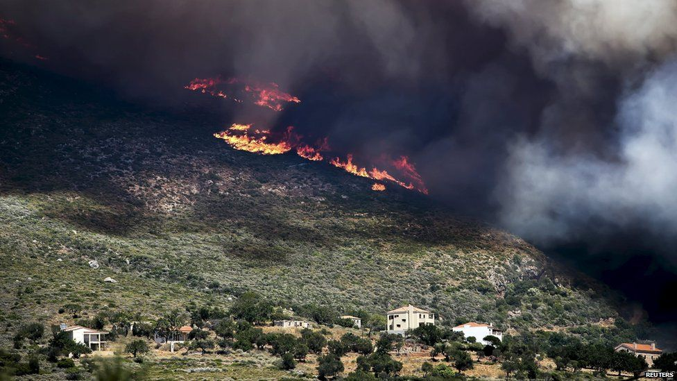 Smoke and flames rise next to houses as a wildfire rages at the village of Neapoli in the region of Laconia in Peloponnese, southern Greece July 17, 2015