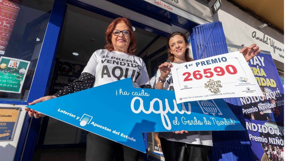 Owner of the lottery administration Virgen de La Salceda, Fuensanta Vicente (R), celebrates selling the first prize ticket in Murcia.